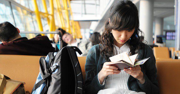 Jeune femme dans un aéroport en train de lire (Istock)