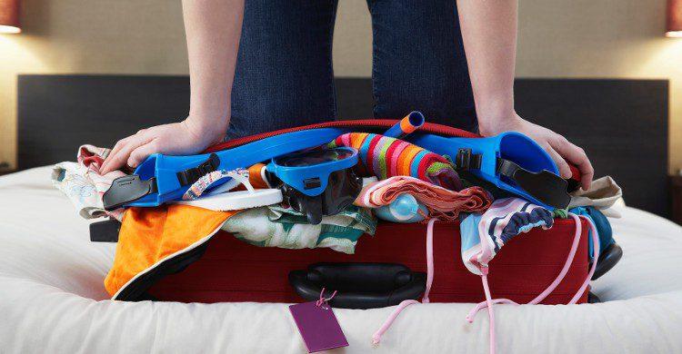 Jeune femme en train de fermer sa valise (Istock)