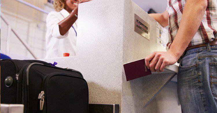 Jeune femme en train de présenter son passeport avant d'embarquer (Istock)