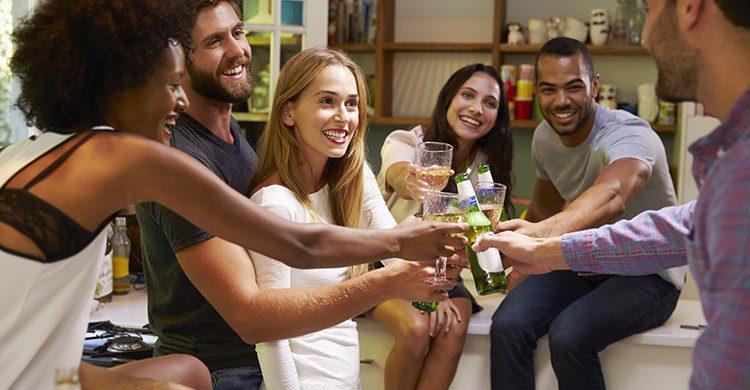 Groupe d'amis en train de trinquer dans un salon (Istock)