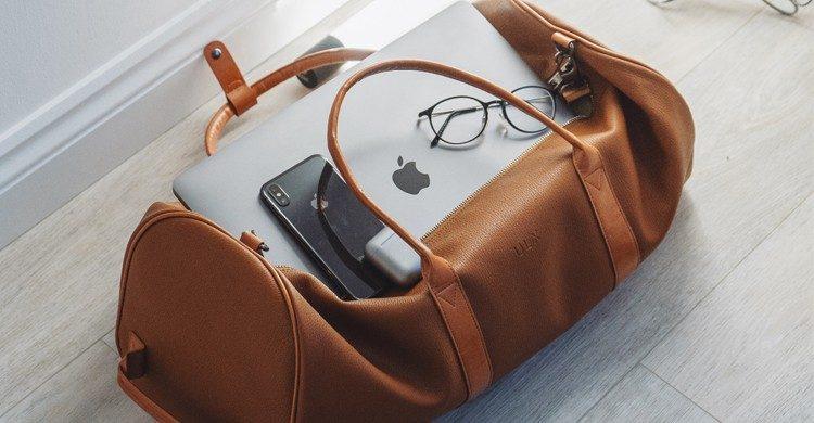 Sac de voyage en cuir ouvert laissant voir un ordinateur portable et des lunettes