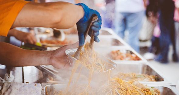 Une barquette de nouilles servie à un stand de streetfood